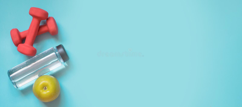 Equipamento do esporte e da aptidão, pesos, água e maçã Configuração lisa criativa no azul punchy Espaço para seu texto imagens de stock royalty free