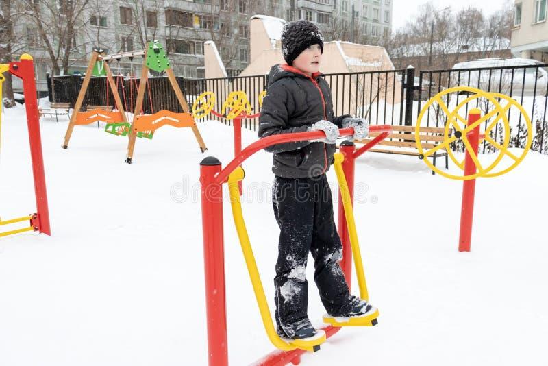 Equipamento do exercício da rua no inverno, na aptidão do esporte exterior e no halterofilismo Menino em um campo de jogos do esp fotografia de stock