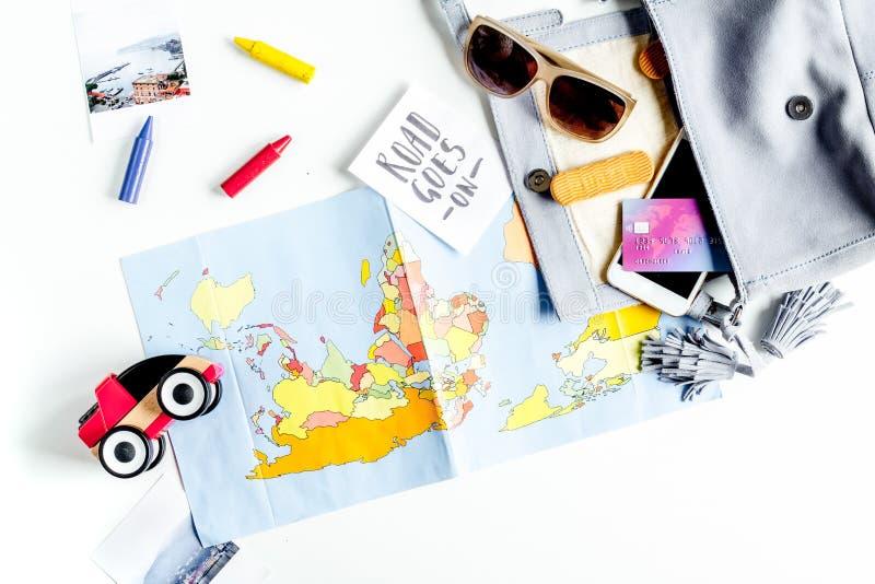 Equipamento do turista com mapa e brinquedos para viajar com as crianças na opinião superior do fundo branco fotos de stock