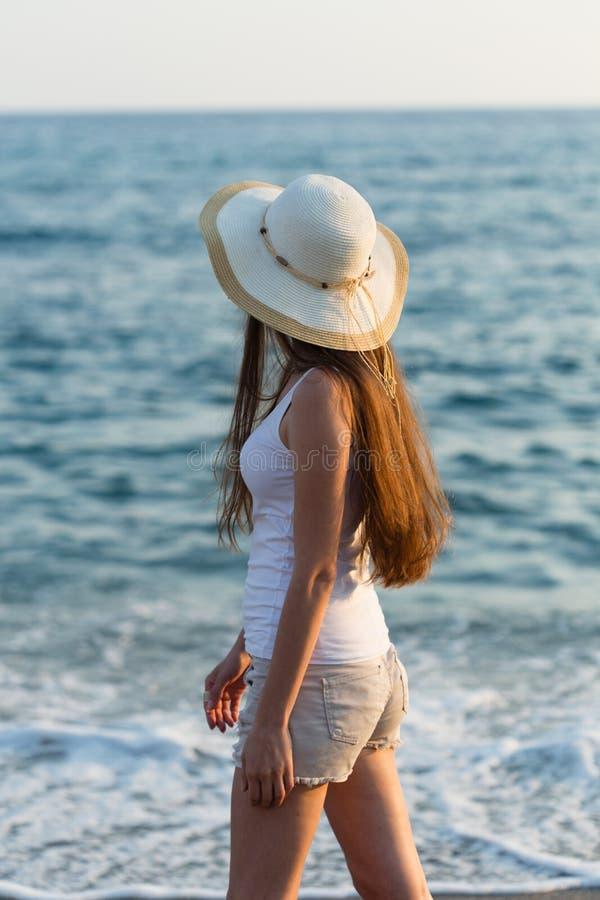 Equipamento do verão da mulher e chapéu de palha vestindo pelo beira-mar fotografia de stock
