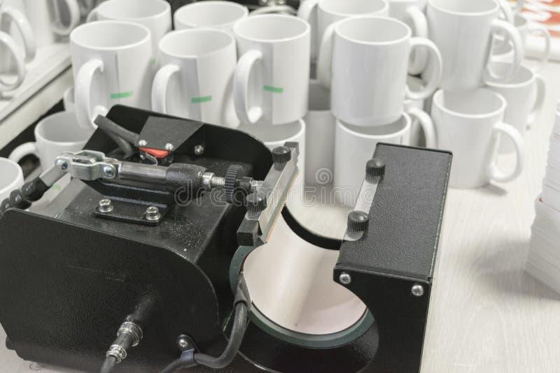 Equipamento e canecas de impressão da sublimação imagem de stock