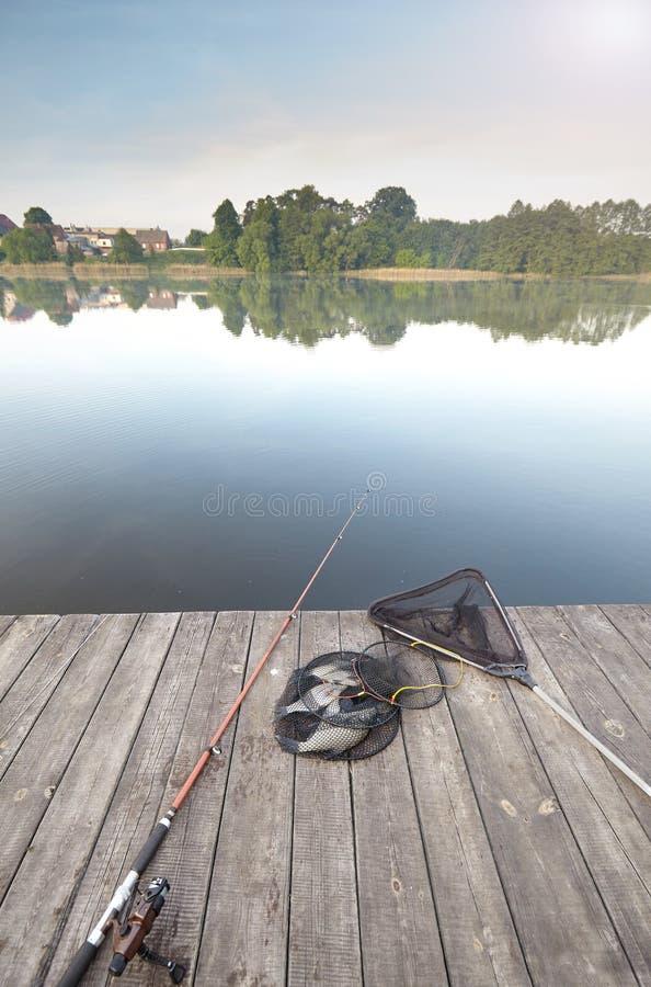 Equipamento e captura de pesca em um cais de madeira imagem de stock