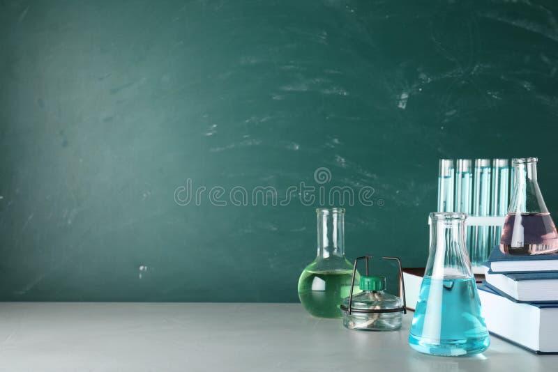 Equipamento e livros de laboratório na tabela perto do quadro com espaço para o texto Química imagem de stock royalty free