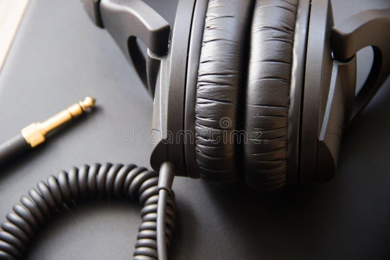 Equipamento musical, fones de ouvido profissionais do preto do estúdio e cabo do jaque Feche acima de cima de imagens de stock royalty free