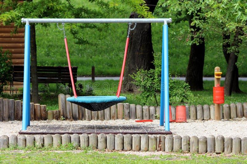 Equipamento público exterior colorido do campo de jogos na forma do grande balanço feita da rede forte suspendida acima de borrac imagens de stock