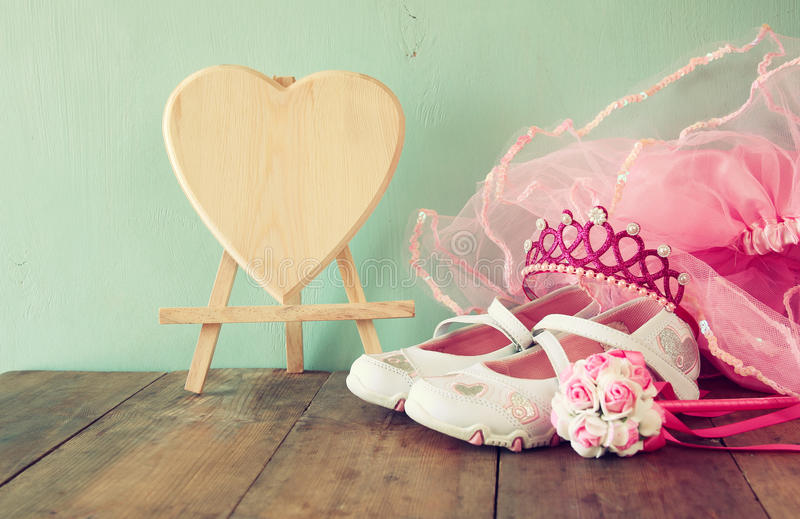 Equipamento pequeno do partido das meninas: flores brancas das sapatas, da coroa e da varinha na tabela de madeira traje da dama  imagens de stock