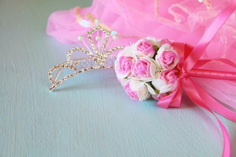 Equipamento pequeno do partido das meninas: flores da coroa e da varinha na tabela de madeira traje da dama de honra ou da fada F imagens de stock