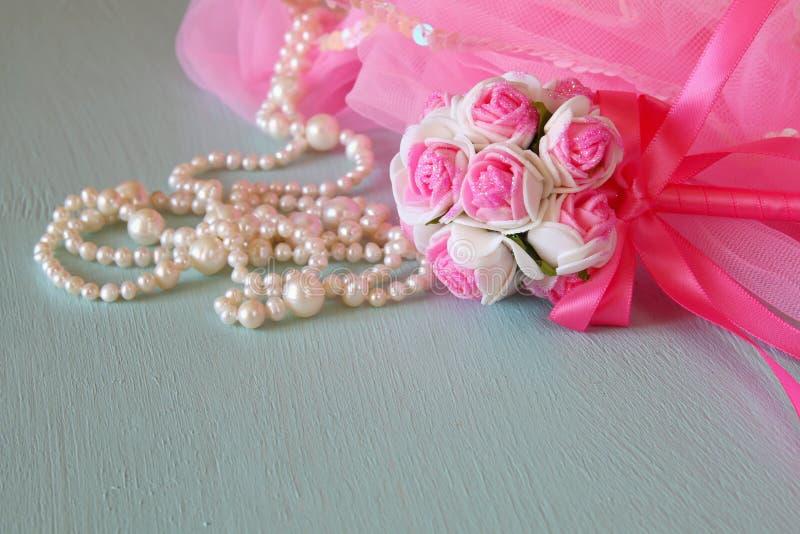 Equipamento pequeno do partido das meninas: flores da coroa e da varinha na tabela de madeira traje da dama de honra ou da fada F fotografia de stock