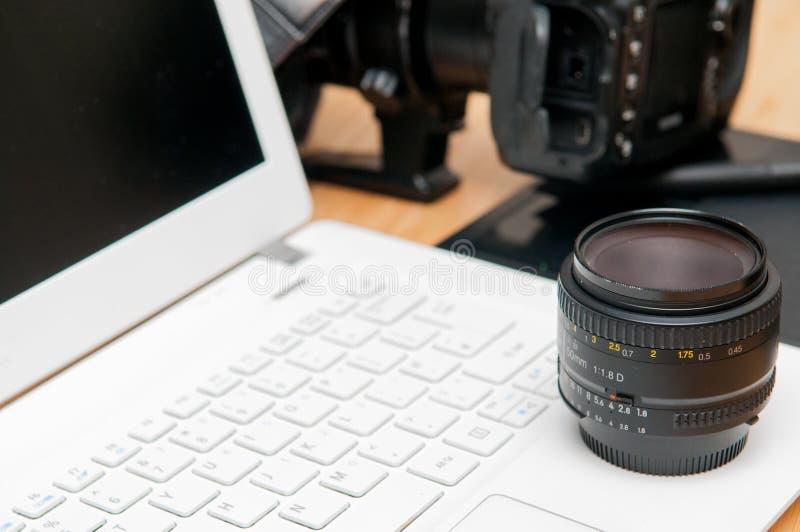 Equipamento profissional da edição da fotografia com câmera e lapto imagens de stock