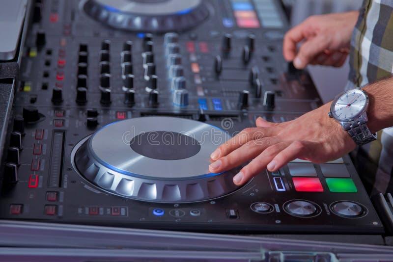 Equipamento profissional da música para a música do jogo e do controle no clube noturno com mãos DJ O DJ mistura a trilha no club imagem de stock