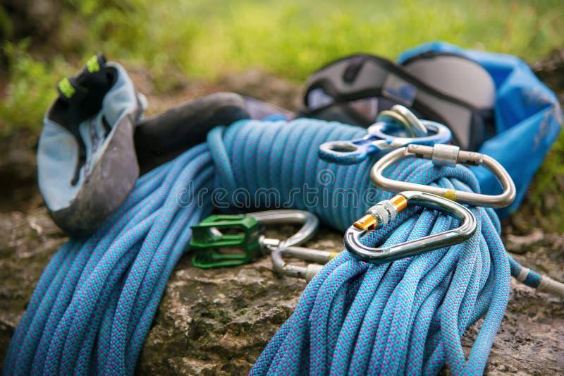 Equipamento usado para escalar onde as carabinas da corda e os deslizadores de escalada se encontram em uma rocha imagem de stock