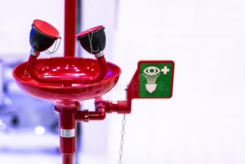 Equipamento vermelho da estação da lavagem do olho da emergência com signage da segurança imagens de stock