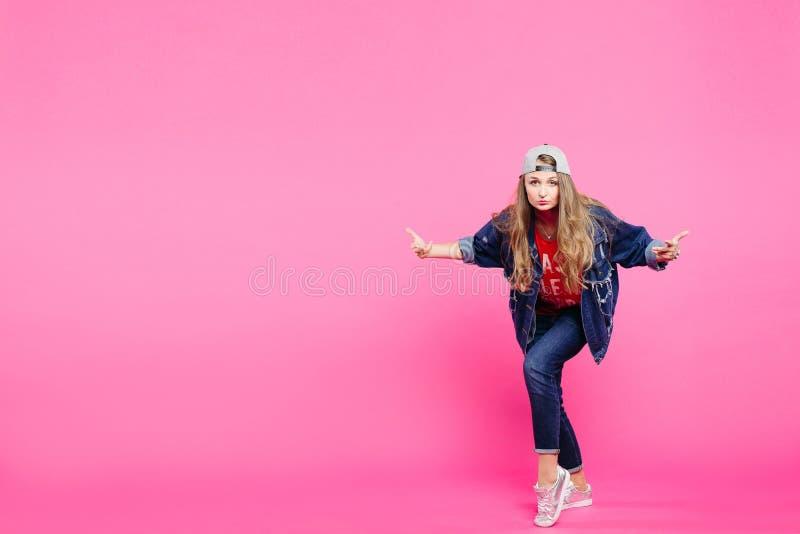 Equipamento vestindo das calças de brim do modelo novo e levantamento no estúdio cor-de-rosa fotografia de stock royalty free