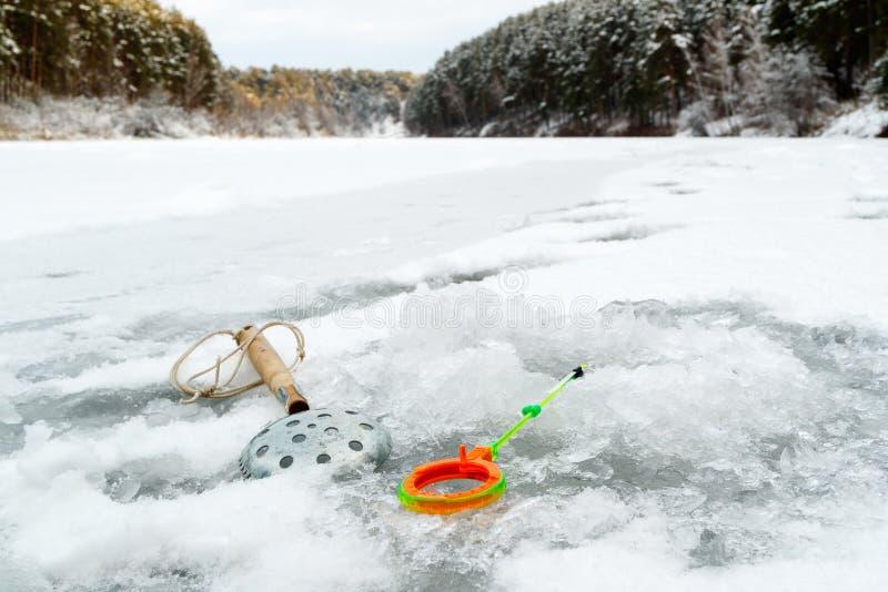 Equipamentos para a pesca do inverno, um dispositivo da gelo-colheita e um polo de pesca perto do furo com água congelada imagem de stock royalty free