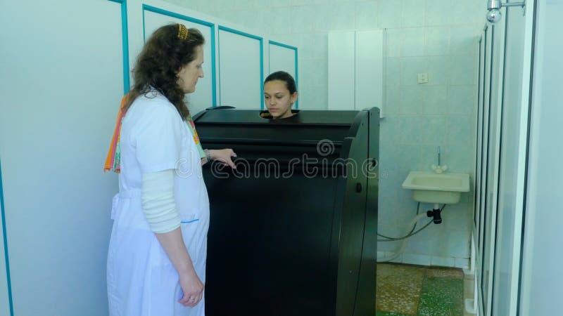 Equipamiento médico Cryotherapy Cápsula de Cryotherapy en clínica cosmetological Mujer joven en un cuerpo completo cryotherapy imagen de archivo