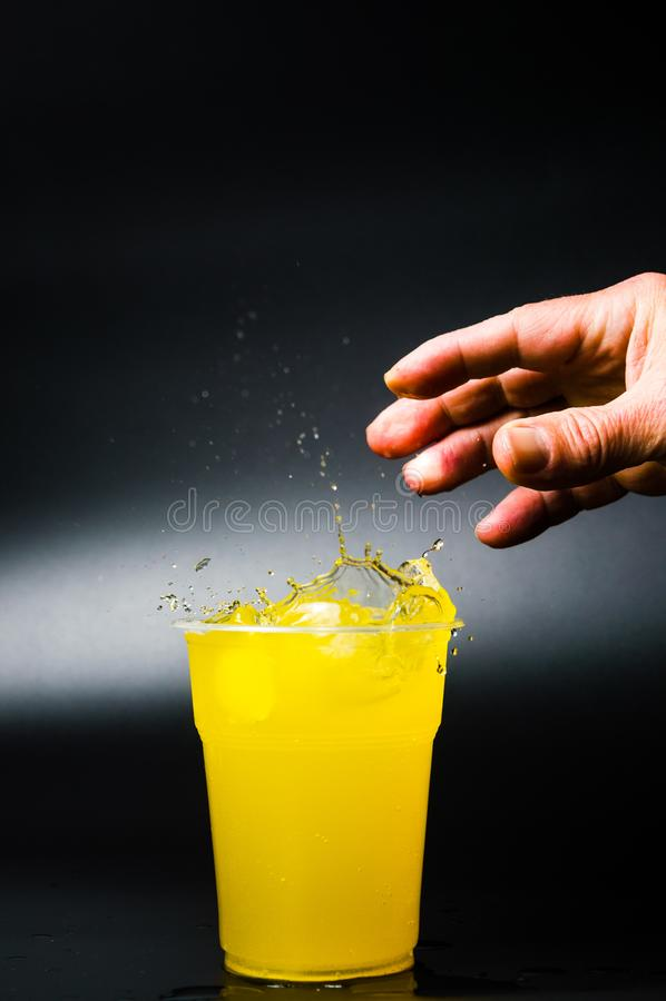 Equipe a adição do gelo no suco de laranja foto de stock