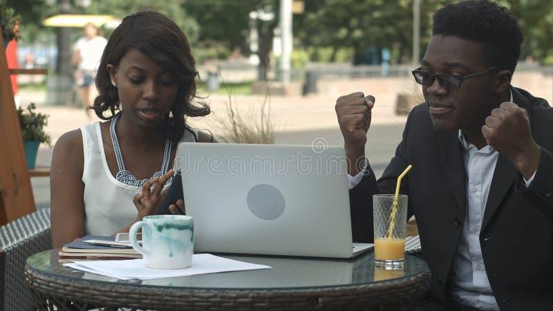 A equipe afro-americana do negócio discute durante a reunião de negócios no café imagem de stock royalty free