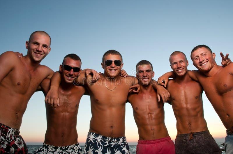 Equipe alegre dos amigos que têm o divertimento na praia imagens de stock royalty free