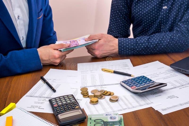 a equipe analisa as despesas de negócio do pressuposto anual, contando euro imagem de stock