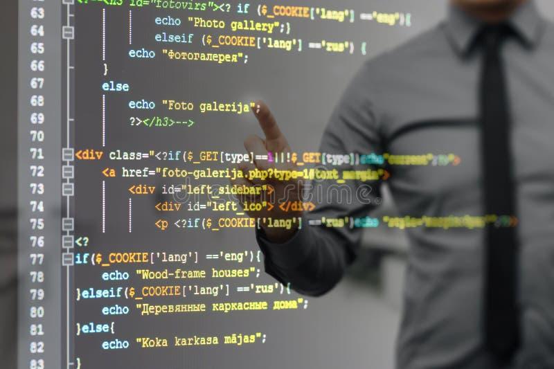 Equipe apontar na tela virtual com código de programação do Web site imagens de stock royalty free