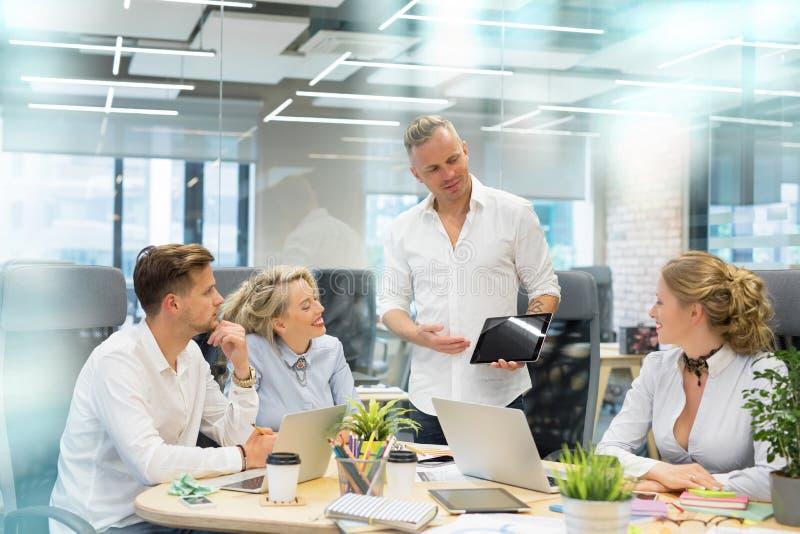 Equipe a apresentação de algo a seus colegas de trabalho na tabuleta imagens de stock