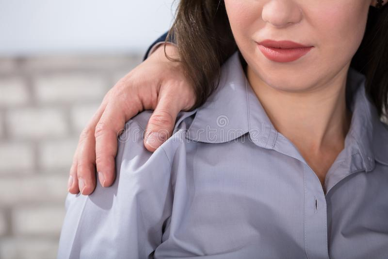 Equipe as mãos do ` s em ombros do ` s da mulher imagem de stock