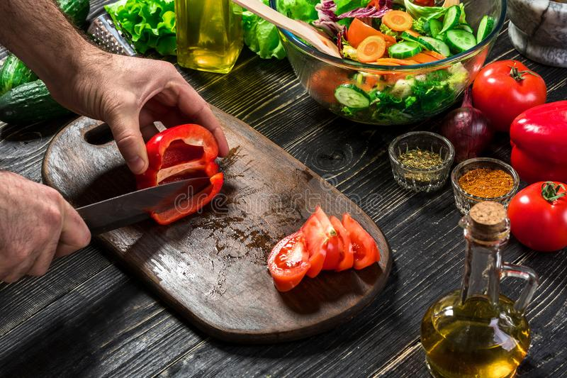 Equipe as mãos do ` s que cortam a paprika vermelha com faca Paprika vermelha cortada cozinheiro O homem ama cozinhar a salada fr foto de stock