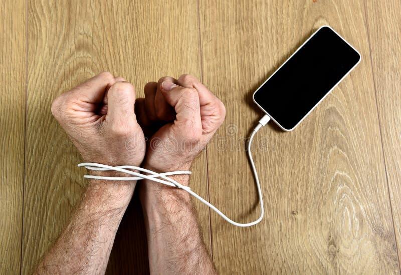 Equipe as mãos envolvidas nos pulsos com o cabo do telefone celular algemado no conceito esperto do apego dos trabalhos em rede d imagens de stock royalty free