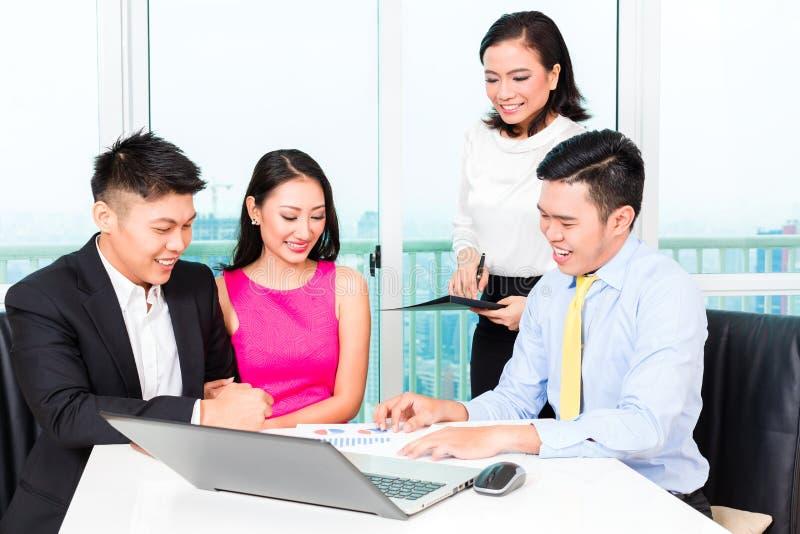 Equipe asiática do banqueiro que aconselha pares no escritório imagem de stock