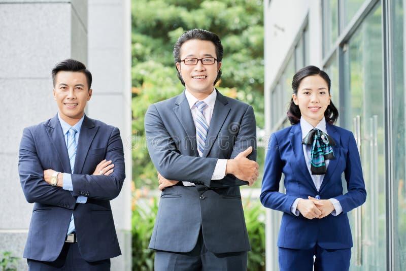 Equipe asiática do negócio que está fora imagem de stock