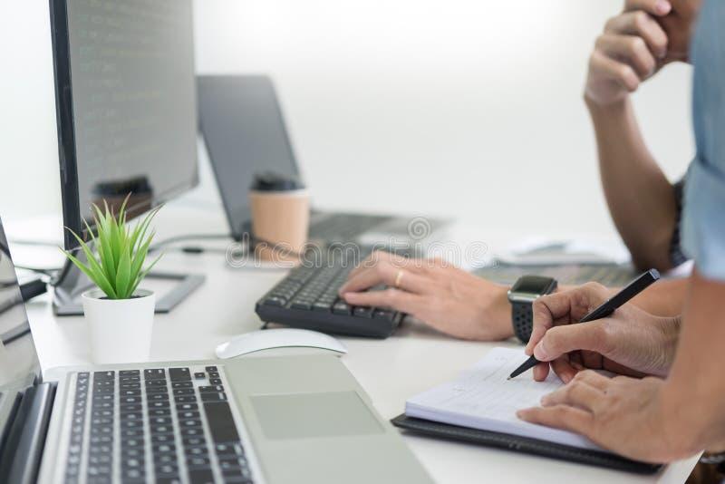 A equipe asiática externaliza o colaborador que olha o funcionamento de programação do código da tela com software de laptop imagem de stock