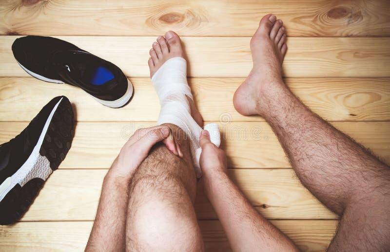 Equipe a atadura do pé que senta-se no assoalho de madeira fotos de stock