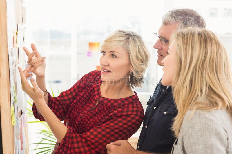 Equipe atenta do negócio que olha notas na parede imagem de stock