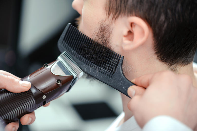 Equipe barbeações sua barba com uma tosquiadeira de cabelo foto de stock royalty free
