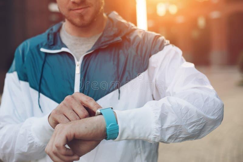 Equipe a batida da tela de relógios espertos, por do sol na rua fotografia de stock royalty free