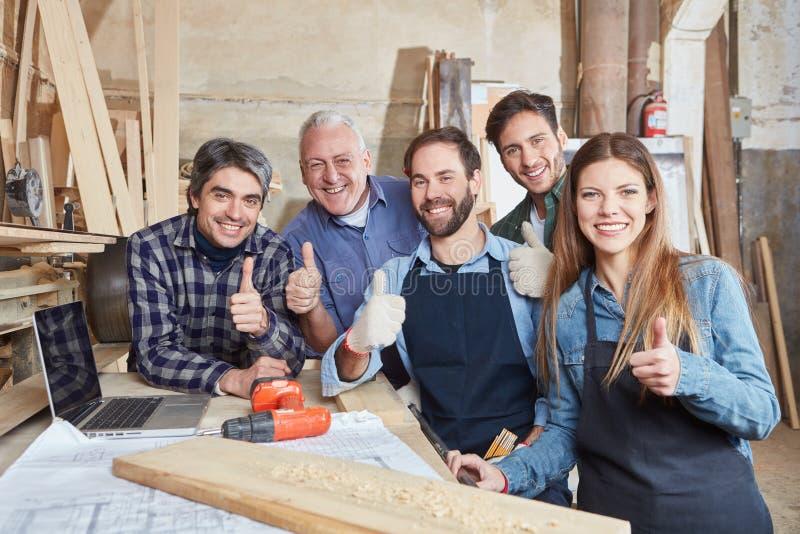 Equipe bem sucedida do artesão que mantém os polegares fotos de stock royalty free