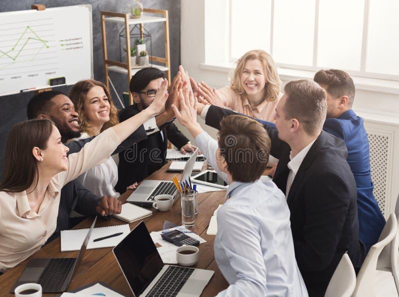 A equipe bem sucedida do negócio está dando a elevação cinco imagens de stock