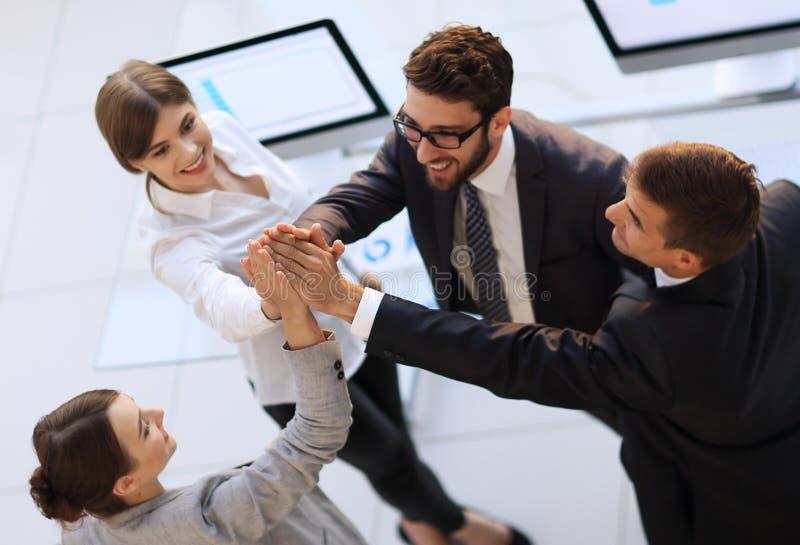 Equipe bem sucedida do negócio que dá-se uma alta-cinco, posição no escritório fotografia de stock royalty free
