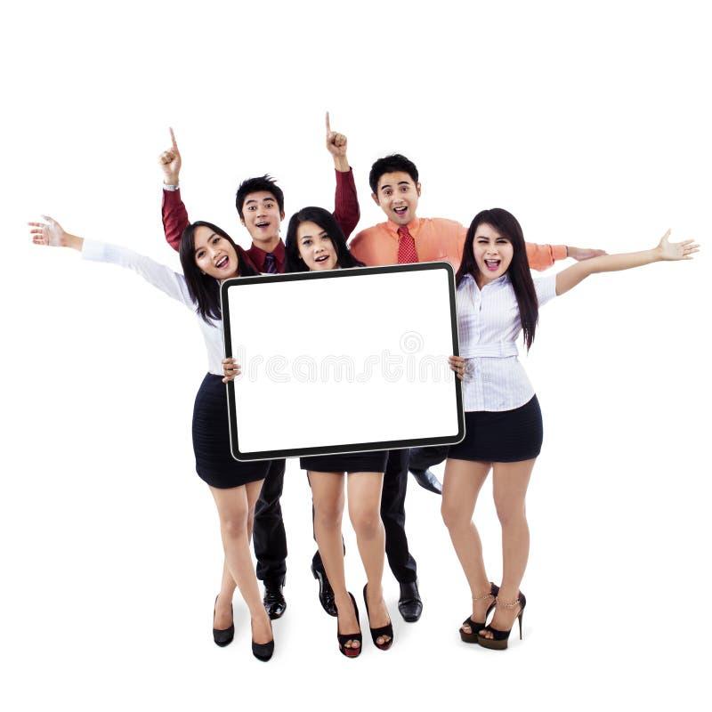 Equipe bem sucedida do negócio que mostra a placa vazia fotografia de stock royalty free