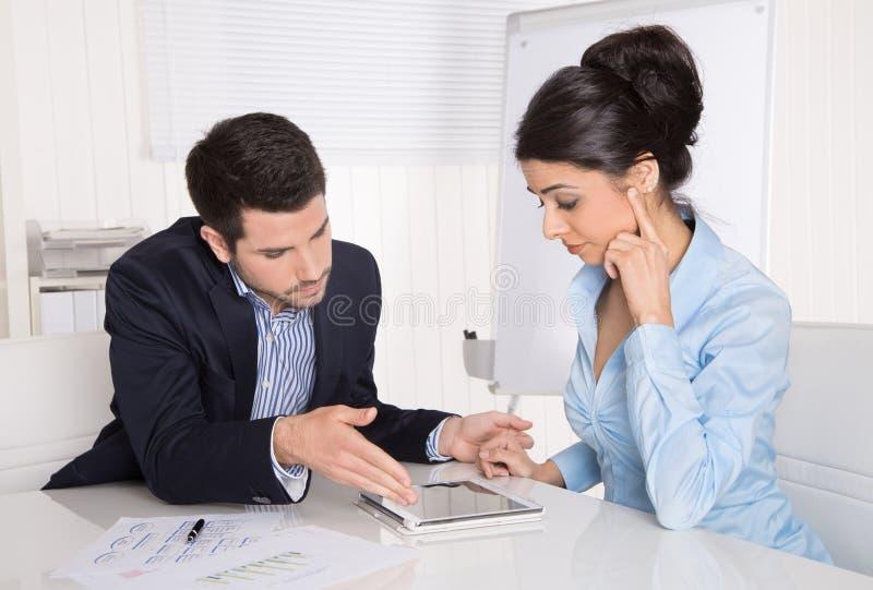 Equipe bem sucedida do negócio que senta-se na mesa que olha o compu da tabuleta foto de stock royalty free