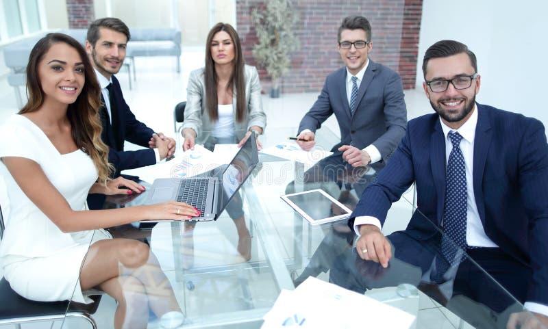 Equipe bem sucedida do negócio que senta-se no DES do escritório foto de stock royalty free