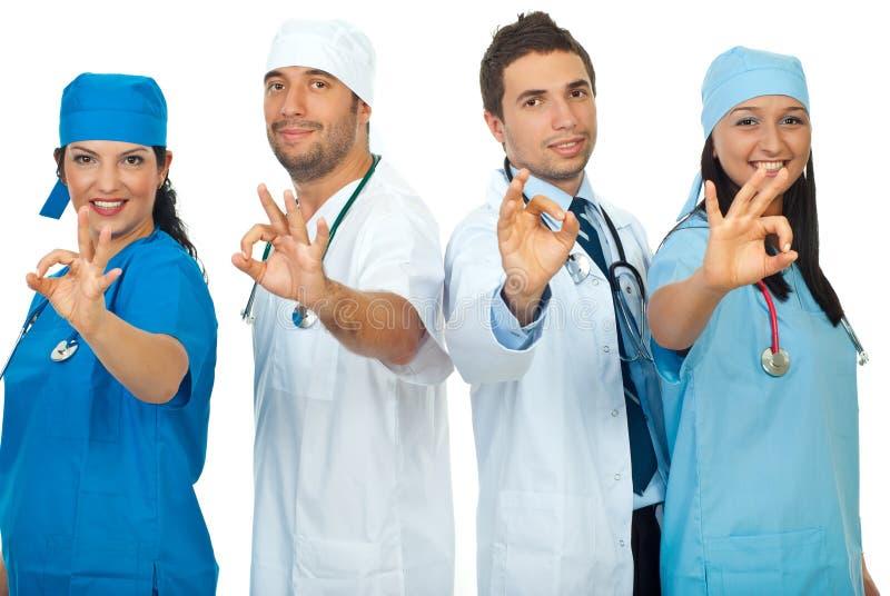Equipe bem sucedida dos doutores que mostra o sinal aprovado imagens de stock