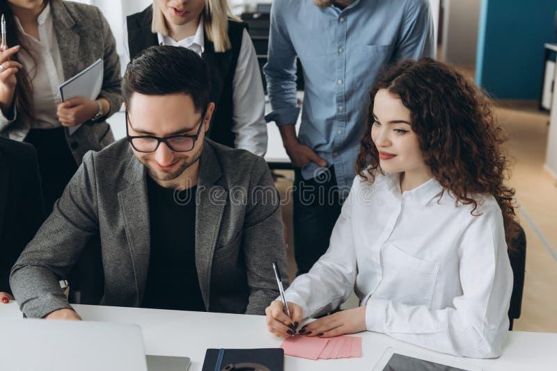 Equipe bem sucedida Grupo de executivos novos que trabalham e que comunicam-se junto no escrit?rio criativo foto de stock royalty free