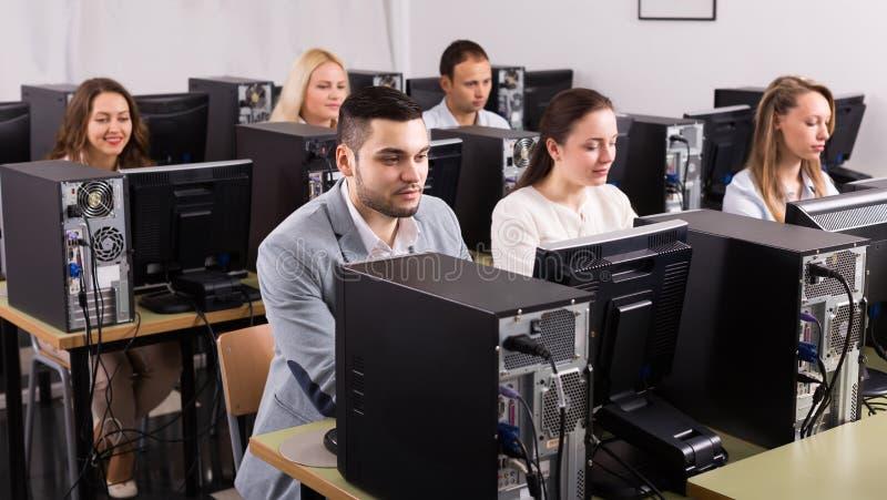 Equipe bem sucedida no PC no escritório imagens de stock royalty free