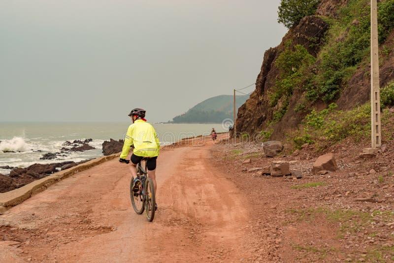 Equipe a bicicleta da equitação na estrada de terra na cidade de Vinh, Vietname fotos de stock royalty free