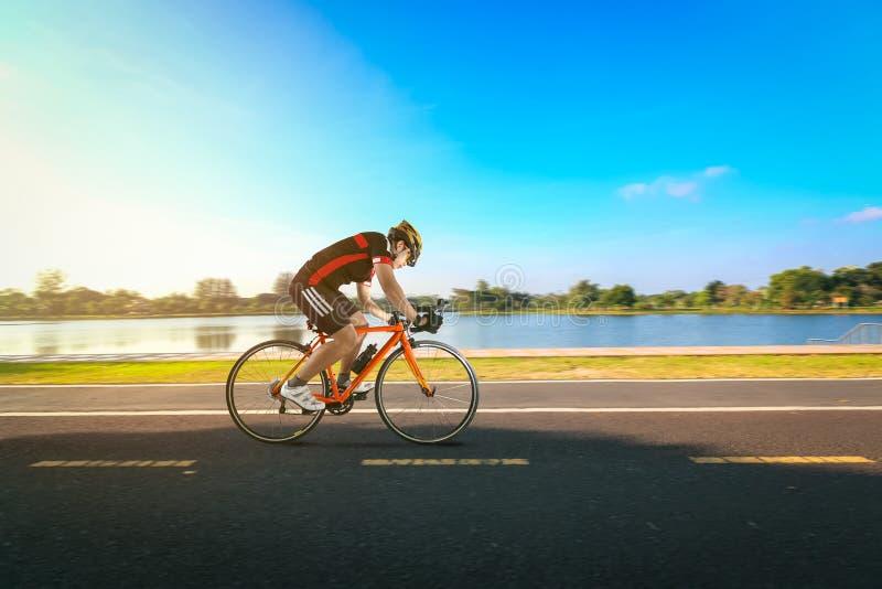 Equipe a bicicleta da equitação no lado da estrada e do rio no parque fotos de stock royalty free