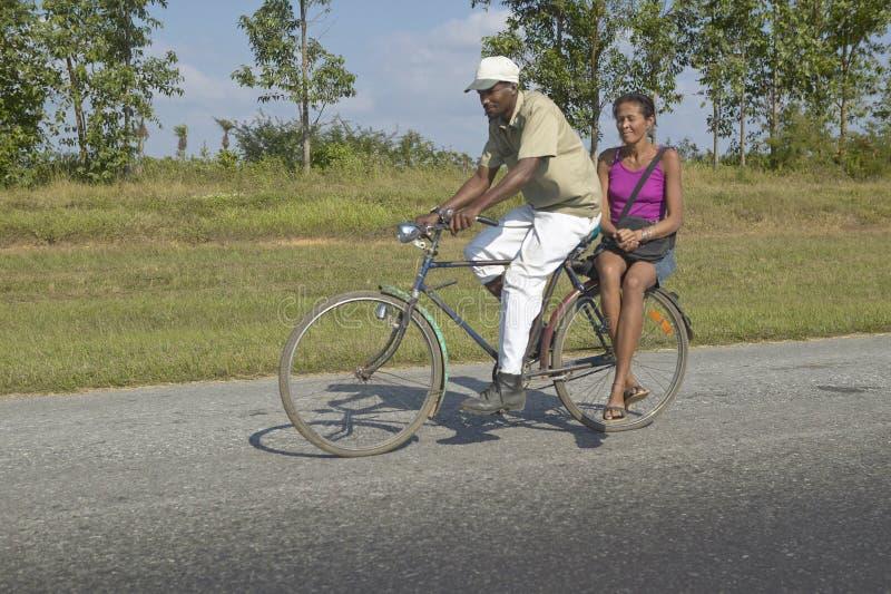 Equipe bicycling com a mulher na parte de trás da bicicleta através do campo de Cuba central fotos de stock