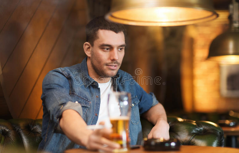 Equipe a cerveja bebendo e o cigarro de fumo na barra imagens de stock royalty free