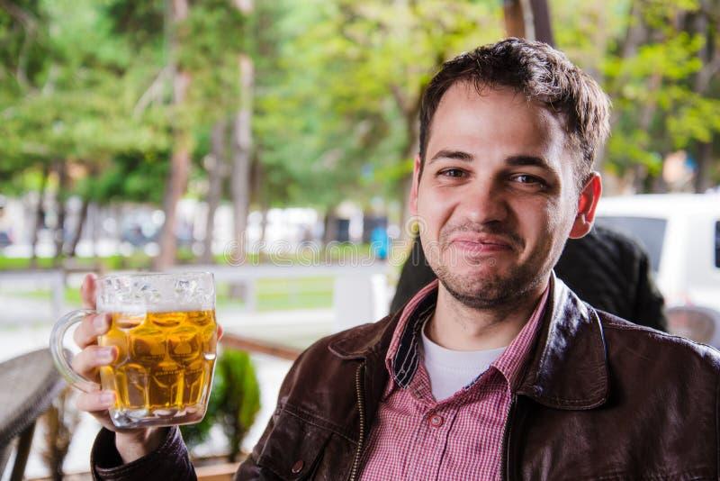 Equipe a cerveja bebendo fora em um café com expressões engraçadas fotografia de stock royalty free