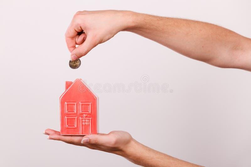 Equipe a colocação da moeda no piggybank da casa imagem de stock royalty free